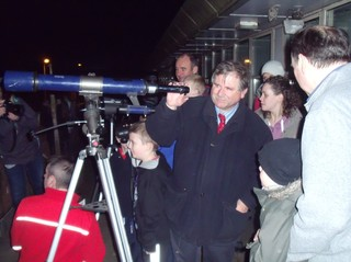 Professor Bailey showing the comet through a telescope